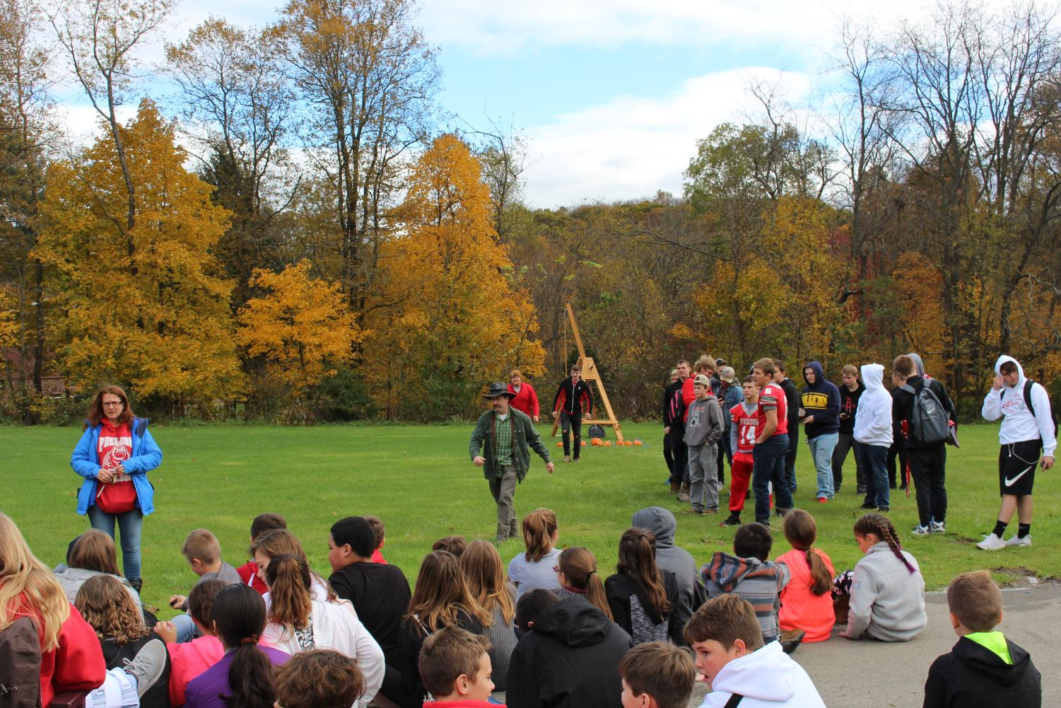 Ging explains the trebucket while the FHS Physics Club, with adviser Brian Wargo, prepares to launch pumpkins. Photo By Logan Bickerstaff