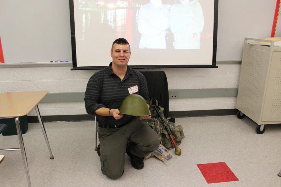 David Hackleroad demonstrates a helmet used in the Iraq war.