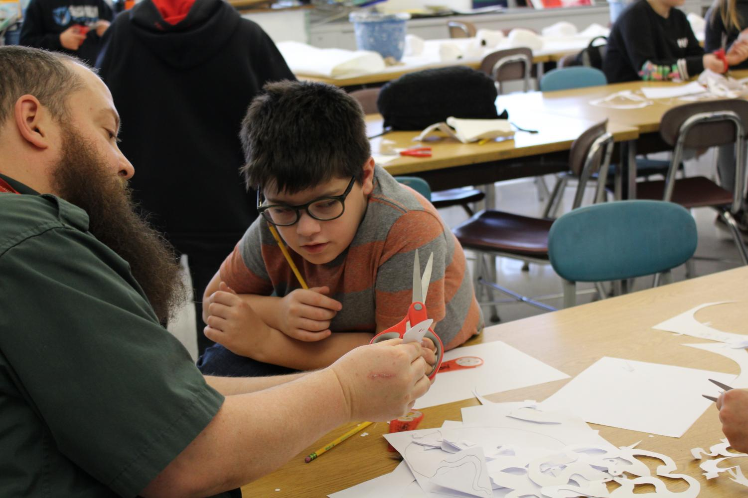 Mr. Gregg, art teacher, demonstrates to fifth grader Sam Giovengo how to cut a snowflake from paper during art class.