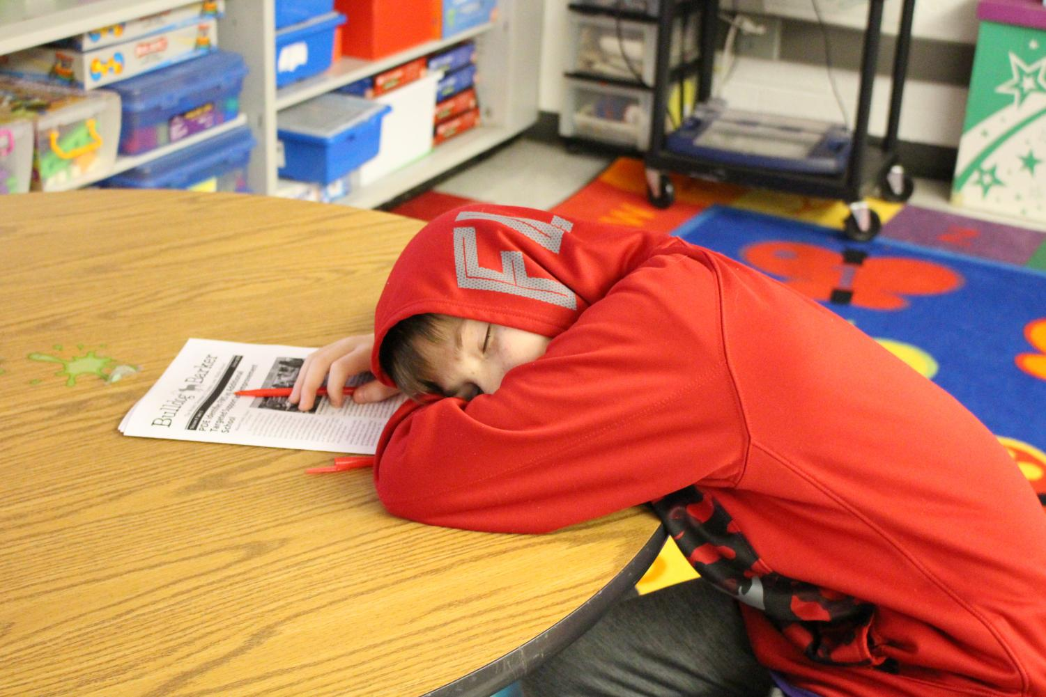 Sixth grader Tyler Misencik falls asleep while editing newspaper articles on Feb. 6 due to lack of sleep.