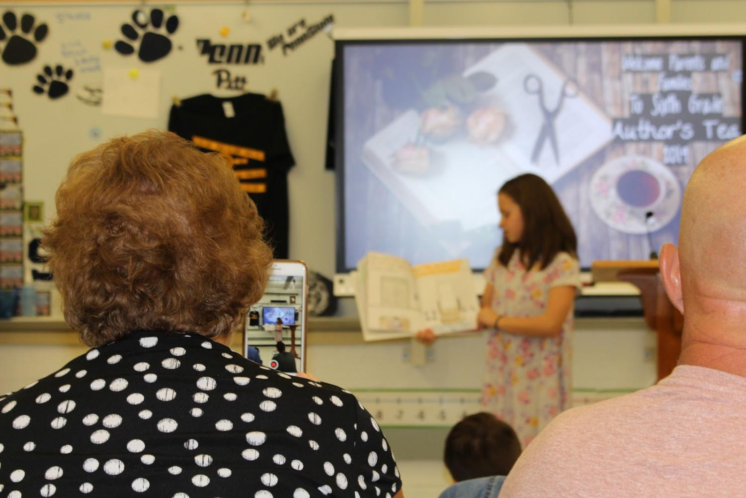 Parents watch as students present their children's book
