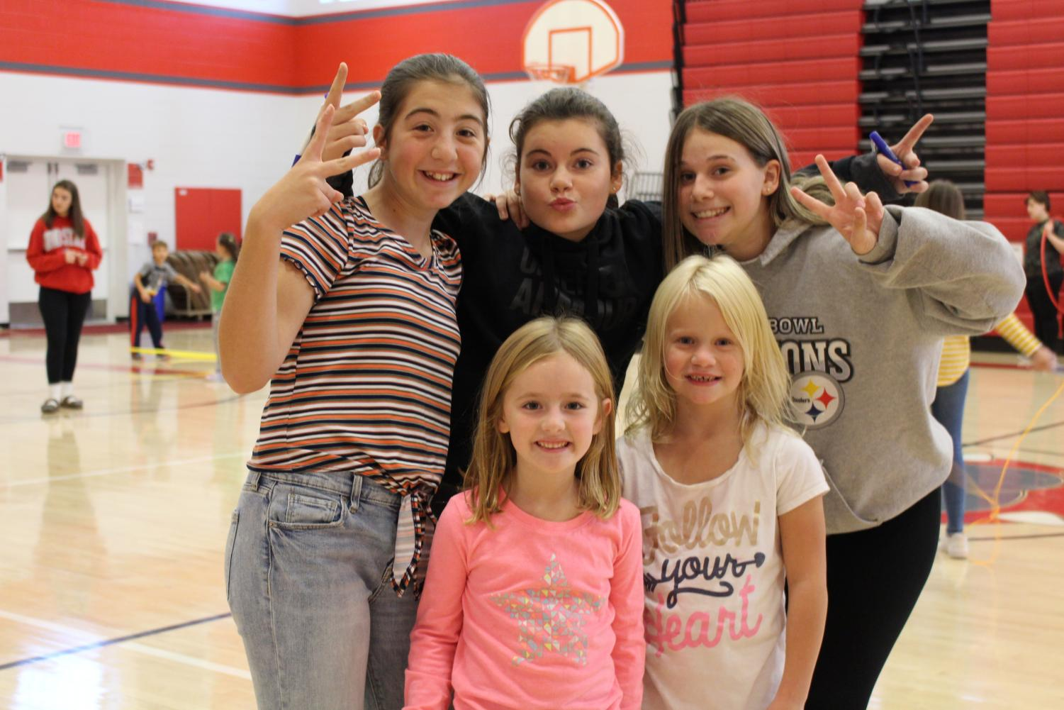 Seventh graders Olivia Henderson, Annabelle Komlos, and Malina Pelaia help first graders Mikaylee Kuntz and Josie Hall jump rope, during their gym class.