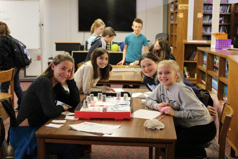 Sixth grade students share their math games with other classes in the library during Academic Support.