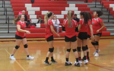 Eighth grade volleyball team warm up before their game.