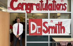 Dr. Smith poses with a sign in front of his office celebrating his doctoral success.